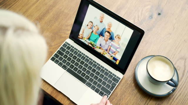 Attractive-Blond-Woman-Flicking-Through-Family-Album-On-Laptop