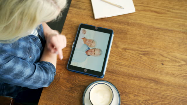 Attractive-Blond-Woman-Swiping-Through-Family-Album-On-Digital-Tablet