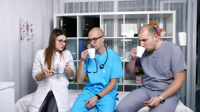 Doctors-in-the-doctor-s-lounge-drinking-coffee-and-talking-on-the-break-