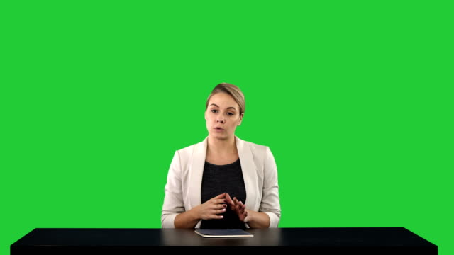 Television-anchorwoman-at-studio-pointing-to-sides-on-a-Green-Screen-Chroma-Key