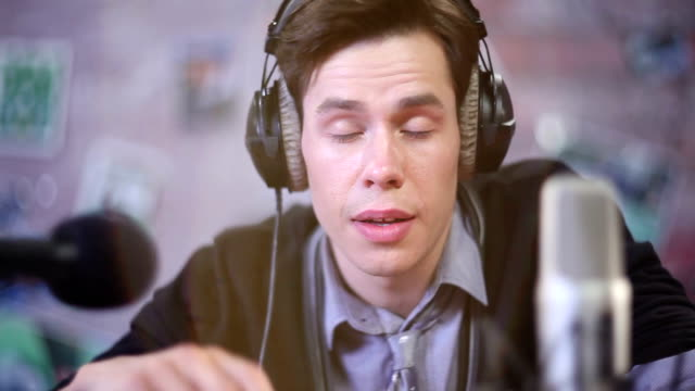 Man-in-headphones-boring-and-lazy-talking-into-microphone-