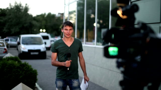 Attractive-professional-male-news-reporter-holding-on-air-microphone-talking-to-camera-in-tv-live-broadcasting