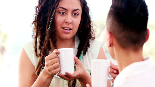 Smiling-lesbian-couple-drinking-coffee-together