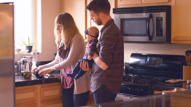 A-young-couple-drinking-their-morning-coffee-in-the-kitchen-while-the-young-man-holds-their-baby