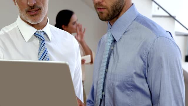 Empresario-hablando-frente-a-la-cámara-mientras-la-empresaria