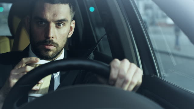 Businessman-Driving-a-Car-in-the-Morning-Drinking-Coffee-