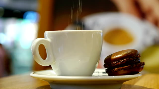 Cup-of-coffee-with-brown-macaron-in-an-indoor-café