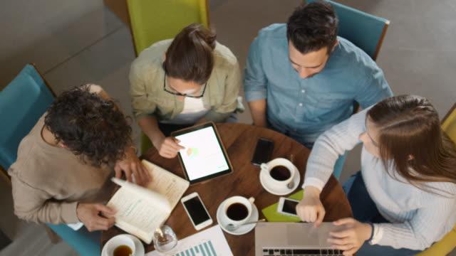 Pequeño-equipo-creativo-de-la-gente-joven-activa-con-reunión-y-discusión-en-la-cafetería-