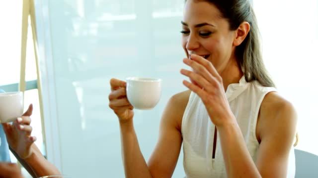 Ejecutivo-sonriente-interactuando-al-mismo-tiempo-que-una-taza-de-café