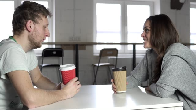 Two-friends-are-sitting-at-the-table-in-cafe-drinking-coffee-to-go-in-paper-cups-and-talking-Shot-in-4k