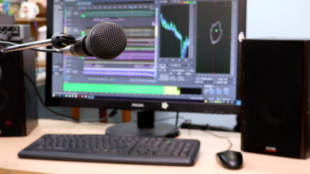 Microphone-on-the-background-of-the-computer-monitor-Home-recording-Studio-Close-up-The-focus-in-the-foreground-Blurred-background-Software-for-recording-and-editing-sounds-4K-UHD-Ultra-HD