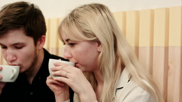 Portrait-of-young-couple-talking-seriously-and-drinking-coffee-at-a-coffee-shop