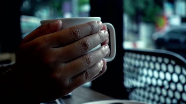 Mano-de-mujer-sosteniendo-una-taza-de-café-en-la-cafetería-en-el-día-de-lluvia