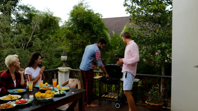 Two-Man-Taking-Food-From-Barbecue-People-Sitting-At-Table-Young-Friends-Group-Gathering-On-Summer-Terrace-Having-Party