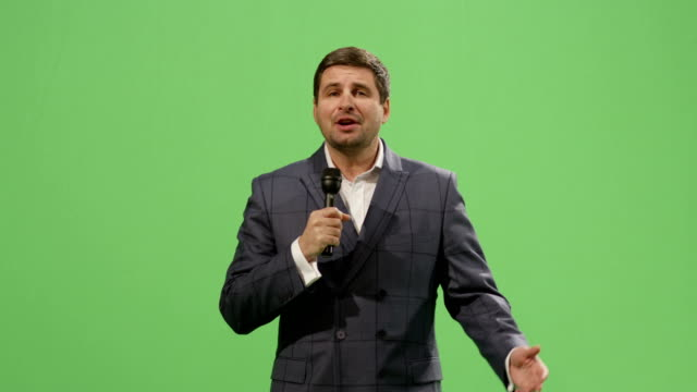 Media-reporter-with-a-microphone-is-talking-on-a-mock-up-green-screen-in-the-background-
