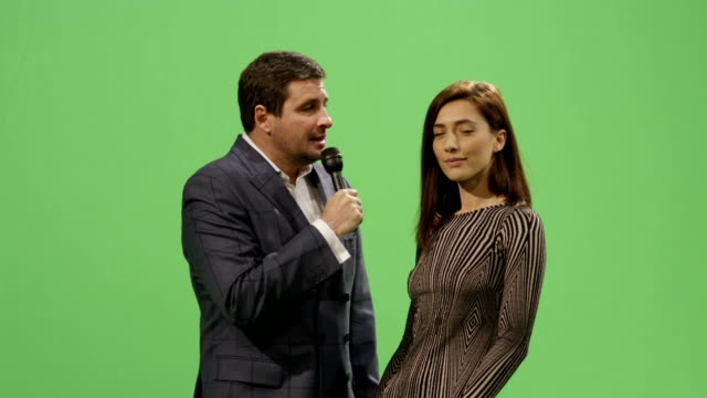 Media-reporter-with-a-microphone-is-taking-an-interview-of-a-woman-in-a-dress-on-a-mock-up-green-screen-in-the-background-