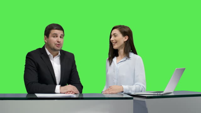 Male-and-female-broadcasters-are-sitting-at-a-table-and-talking-on-a-mock-up-green-screen-in-the-background-