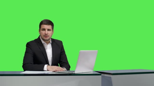 Media-broadcaster-is-sitting-at-a-table-and-talking-on-a-mock-up-green-screen-in-the-background-