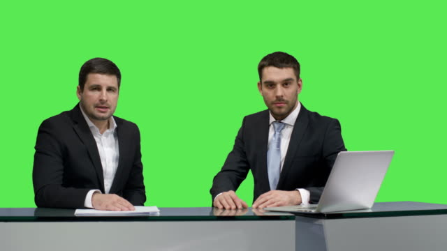 Two-media-broadcasters-are-sitting-at-a-table-with-a-laptop-and-talking-on-a-mock-up-green-screen-in-the-background-