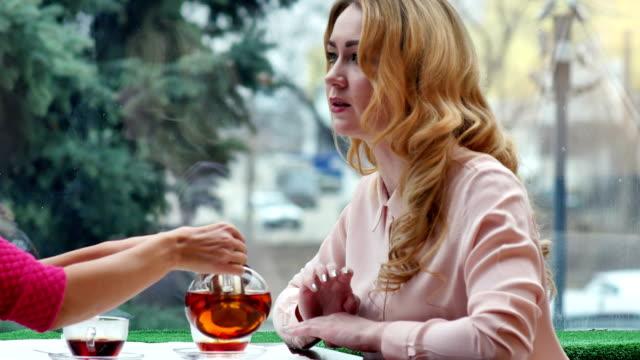 Blonde-enjoying-hot-tea-and-talks-with-friend-in-cafe