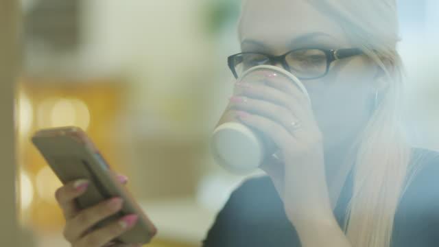 Mujer-bebiendo-café-y-mediante-teléfono-móvil-de-café