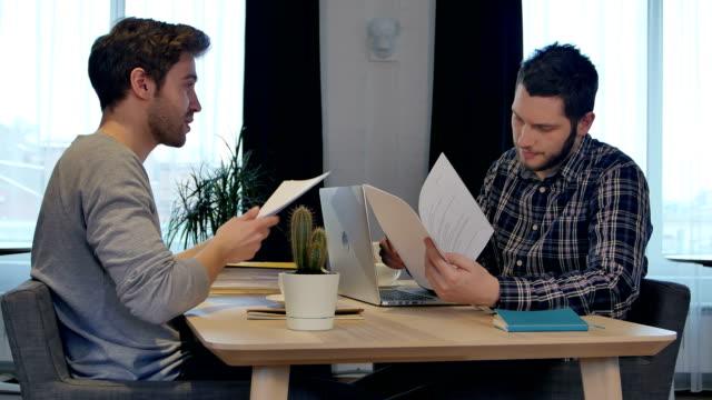 Socios-de-negocios-agitando-las-manos-en-la-oficina-terminando-el-trabajo-con-documentos
