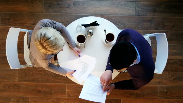 Two-business-people-during-work-meeting-in-modern-cafe