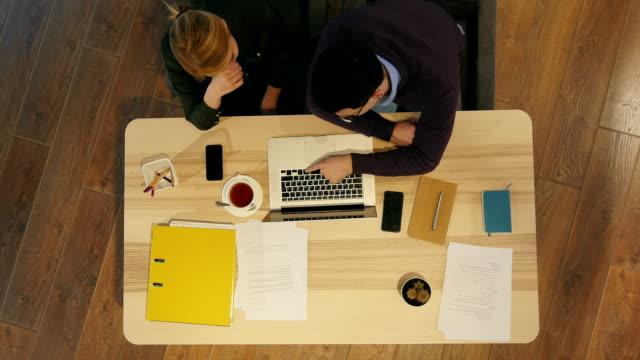 Gerente-y-su-colega-bastante-joven-sentado-en-la-oficina-y-trabajar-en-la-presentación-del-negocio