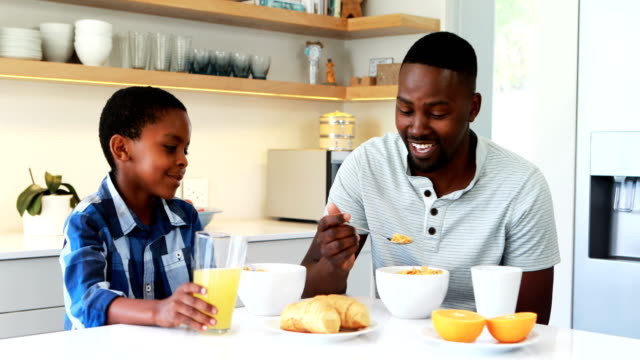 Father-and-son-having-breakfast-in-kitchen