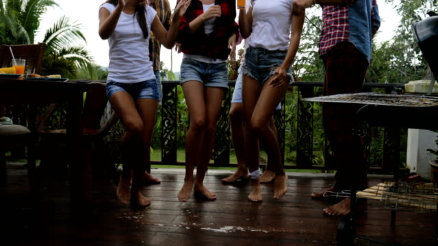Young-People-Dancing-While-Cooking-Barbecue-Frineds-Group-Gathering-On-Summer-Terrace-Having-Party-Legs-Closeup-View