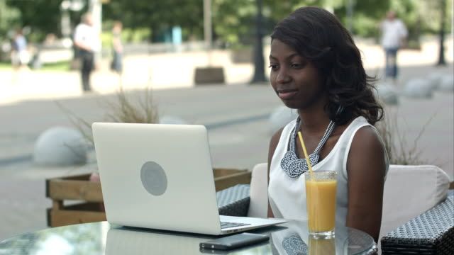 Young-african-woman-sitting-alone-in-a-cafe-having-a-videoconferance-on-a-laptop