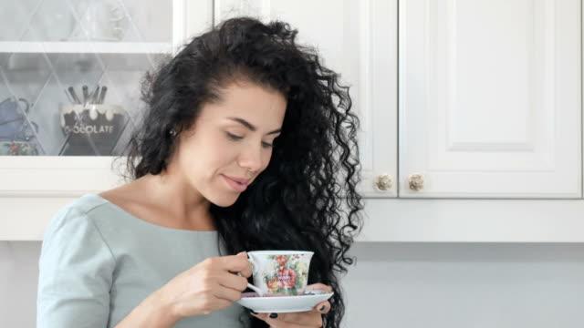 Lächelnde-Frau-trinkt-Kaffee-in-der-Küche