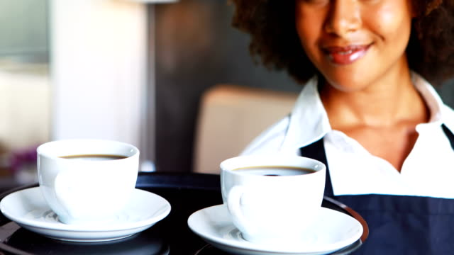 Portrait-of-smiling-waitress-holding-tray-of-coffee-cups