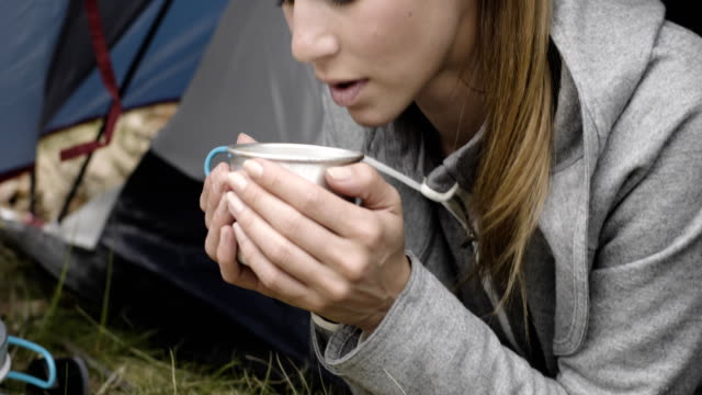 Woman-drinking-hot-beverage-in-camping-tent-Couple-people-in-love-autumn-outdoor-trip-in-nature-Fall-sunny-day-4k-slow-motion-video