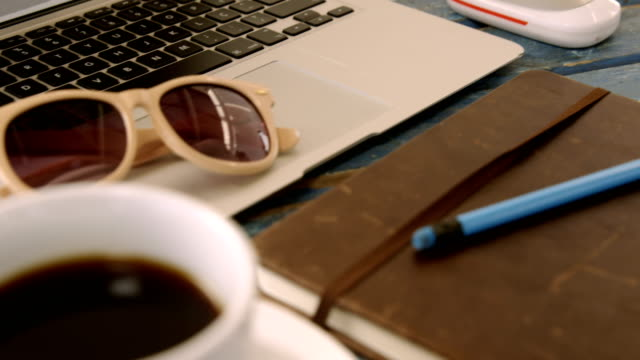 Coffee-organizer-pencil-sunglasses-and-laptop-on-table-4k