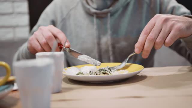 Unrecognizable-man-eating-dessert-strudel-at-the-restaurant-using-fork-and-knife