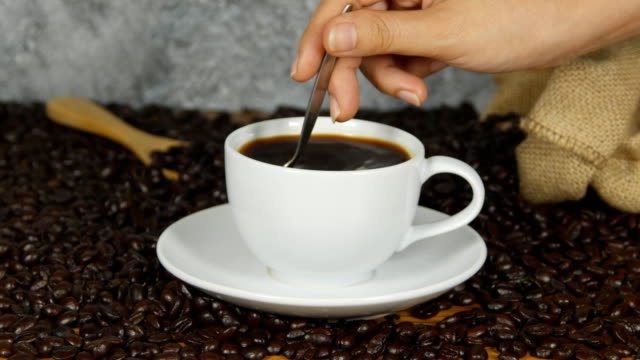 4k-of-Close-Up-Female-Hand-Stirring-Cup-Black-Coffee---female-hand-using-spoon-to-stir-freshly-brewed-ground-black-coffee-white-cup-saucer-beside-whole-coffee-beans-Coffee-time