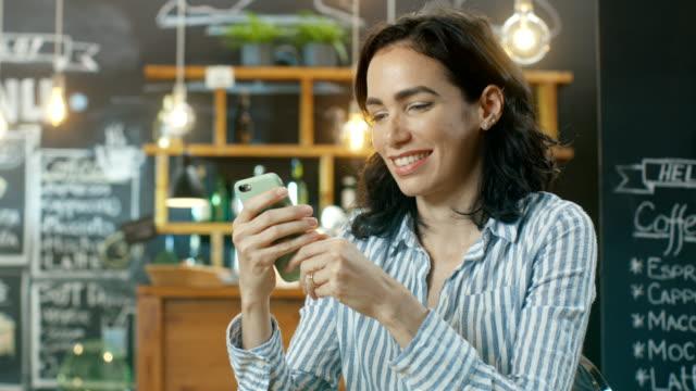 Schöne-Frau-nutzt-Smartphone-beim-Sitzen-im-Cafe-Hintergrund-dieses-stilvolle-Café-