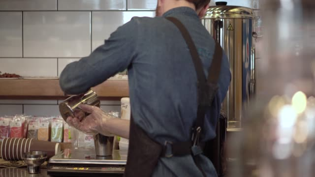 Young-barista-guy-pours-a-milk-mix-into-a-shaker-to-prepare-a-protein-cocktail