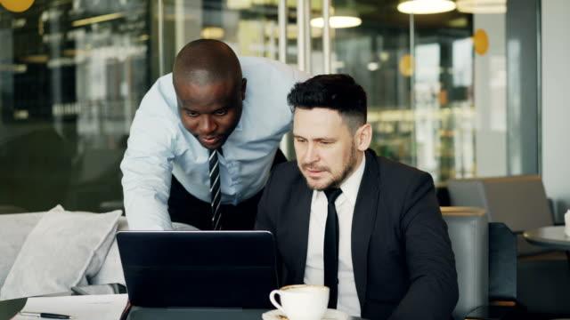 Zwei-Geschäftspartner-diskutieren-aktiv-ihre-Startprojekt-in-stilvollen-Café-sitzen-Bärtige-Geschäftsmann-sitzt-Ang-sprechen-seine-Kollegin-beim-betrachten-Laptop-computer