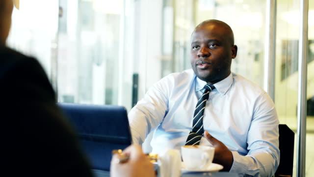 Afrikanische-amerikanische-Geschäftsmann-gestikulierend-und-erklären-seine-Start-up-Daten-für-Anleger-in-Abendgarderobe-in-gläsernen-Café-während-der-Mittagszeit