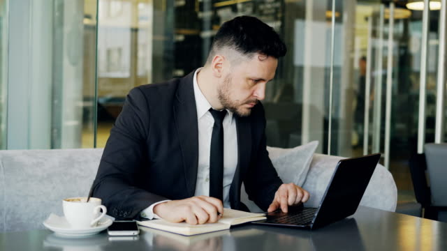 Smart-Caucasian-businessman-using-laptop-computer-and-writing-down-information-in-his-notepad-in-glassy-cafe-having-coffee-cup-on-his-table-