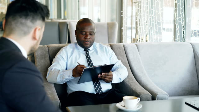 African-american-HR-manager-having-job-interview-with-young-man-in-suit-and-watching-his-resume-application-in-modern-cafe-during-coffee-break