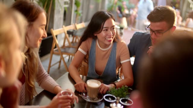Young-multi-ethnic-hipster-couple-relaxing-and-drinking-coffee-with-friends