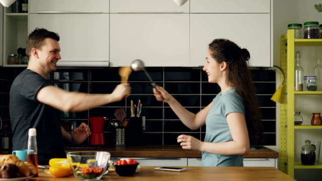Happy-couple-having-fun-in-the-kitchen-fencing-with-big-spoons-while-cooking-breakfast-at-home