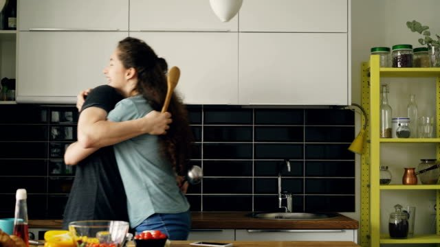 Happy-couple-having-fun-in-the-kitchen-fencing-with-big-spoons-and-embracing-each-other-while-cooking-breakfast-at-home