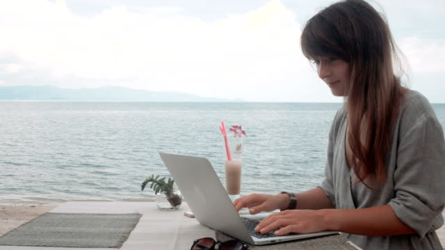 Young-Woman-works-on-laptop-in-outdoor-cafe-moving-camera-stabilizer-shot