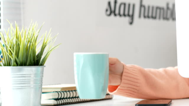 Young-woman-drinking-coffe-and-working-desk-top-PC-at-home-office-