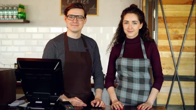 Retrato-de-dos-camareros-guapos-jóvenes-de-pie-en-el-mostrador-del-cajero-de-cafetería-y-sonriendo-Negocios-exitosos-gente-alegre-y-concepto-de-servicio-de-alimentos-