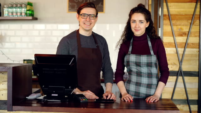 Retrato-de-dos-socios-a-propietarios-de-pequeños-negocios-de-pie-en-el-mostrador-del-cajero-de-cafetería-y-sonriendo-Negocios-exitosos-gente-alegre-y-concepto-de-servicio-de-alimentos-
